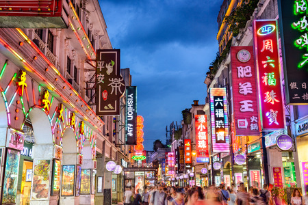 guangdong: GUANGZHOU, CHINA - MAY 25, 2014: Pedestrians pass through Shangxiajiu Pedestrian Street. The street is the main shopping district of the city and a major tourist attraction.