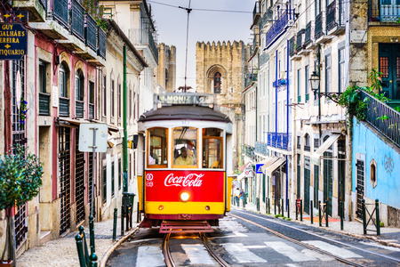trams: LISBON, PORTUGAL - SEPTEMBER 12, 2014: A tram passes the Lisbon Cathedral. The historic trams are a popular attraction. Editorial