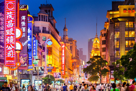 SHANGHAI, CHINA - JUNE 16, 2014: Neon signs lit on Nanjing Road. The area is the main shopping district of the city and one of the worlds busiest shopping streets. 新聞圖片