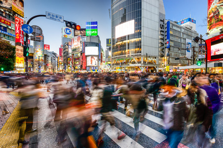 TOKYO, JAPAN - DECEMBER 14, 2012: Pedestrians walk at Shibuya Crossing during the holiday season. The scramble crosswalk is one of the largest in the world. Publikacyjne