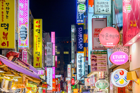 dark city: SEOUL - FEBRUARY 14, 2013: The neon lights of Myeong-Dong. The location is the premiere district for shopping in the city. Editorial