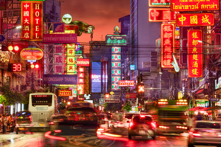 chinatown: BANGKOK, THAILAND - SEPTEMBER 27, 2015: Traffic on Yaowarat Road passes below lit signs in the Chinatown district at dusk. Editorial