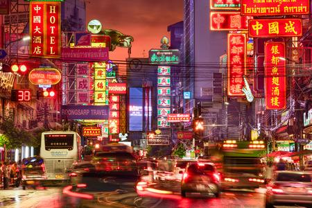 BANGKOK, THAILAND - SEPTEMBER 27, 2015: Traffic on Yaowarat Road passes below lit signs in the Chinatown district at dusk. Sajtókép