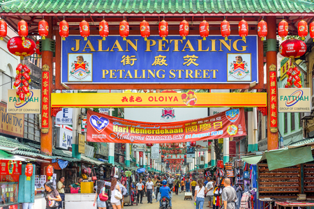 entranceway: KUALA LUMPUR, MALAYSIA - SEPTEMBER 18, 2015: Crowds pass below the main gate of Chinatown at Petaling Street.