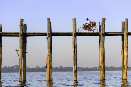 teakwood: MANDALAY, MYANMAR - OCTOBER 26, 2015: A cyclist pushes his bike across the U Bein Bridge over Taungthaman Lake. The bridge was built around 1850 and is the oldest and longest teakwood bridge in the world. Editorial