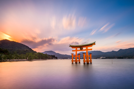 and in asia: Miyajima, Hiroshima, Japan at the great gate of Itsukushima shrine. (gate sign reads Itsukushima Shrine)