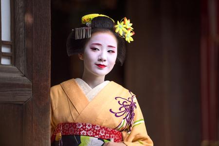 京都市、日本 - 2015 年 11 月 28 日: 伝統的な麻衣子寺院戸口の外に見えるに扮した女性。