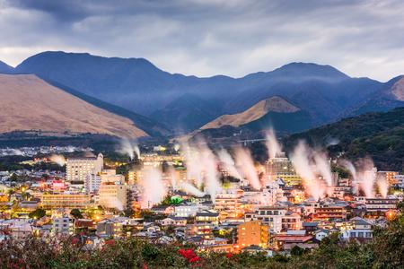 Beppu, Japón del paisaje urbano con las casas de baño de aguas termales con vapor de levantamiento.