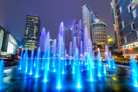 Kuala Lumpur, Malaysia night cityscape and fountain in the financial district.