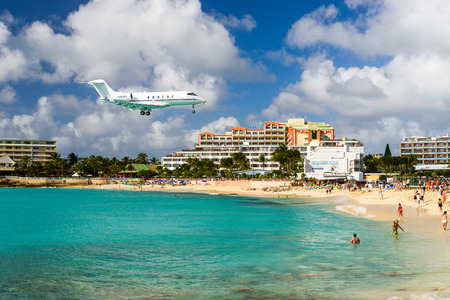 juliana: PHILIPSBURG, SINT MAARTEN - DECEMBER 30, 2013: A jet approaches Princess Juliana Airport above onlookers on Maho Beach. The short runway gives beach goers close proximity views of the planes.