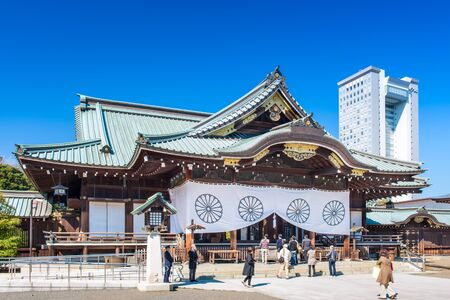 controversial: TOKYO, JAPAN - MARCH 23, 2014: A security guard stands at the entrance to Yasukuni Shrine. The shrine is one of the most controversial in Japan housing the remains of 14 class A war criminals.