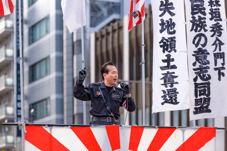 anti fascist: TOKYO - DECEMBER 27, 2015: A right wing speaker gives a public speech in the Asakusa district. Though relatively few in number, the right wing groups are known for highly visible demonstrations.