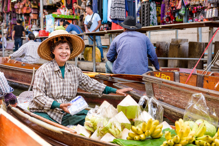 merchant: KANCHANABURI, THAILAND - OCTOBER 7, 2015: A merchant sales her goods at the Damnoen Saduak Floating Market outside of Bangkok.