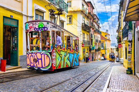LISBON, PORTUGAL - SEPTEMBER 12, 2014: Pedestrians and trams in Lisbon. The historic trams are a popular attraction. Publikacyjne
