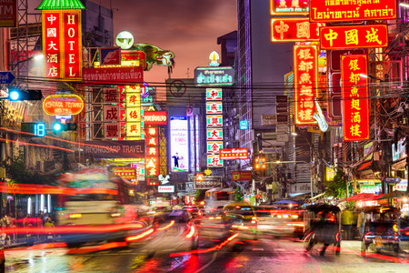 BANGKOK, THAILAND - SEPTEMBER 27, 2015: Traffic on Yaowarat Road passes below lit signs in the Chinatown district at dusk. Editorial