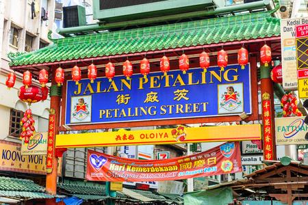 chinatown: KUALA LUMPUR, MALAYSIA - SEPTEMBER 18, 2015: Crowds pass below the main gate of Chinatown at Petaling Street.