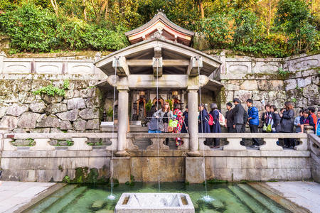 granting: KYOTO, JAPAN - NOVEMBER 30, 2015: Visitors que for the Otowasan waterfalls of Kiyomizudera Shrine. The falls are traditionally believed to have wish granting powers.