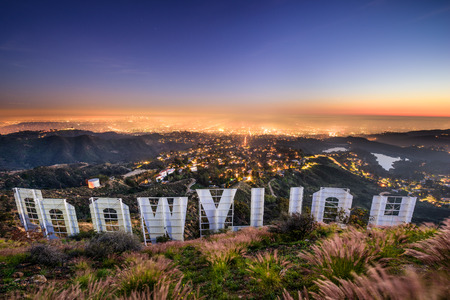 a sign: LOS ANGELES, CALIFORNIA - FEBRUARY 29, 2016: The Hollywood sign overlooking Los Angeles. The iconic sign was originally created in 1923.