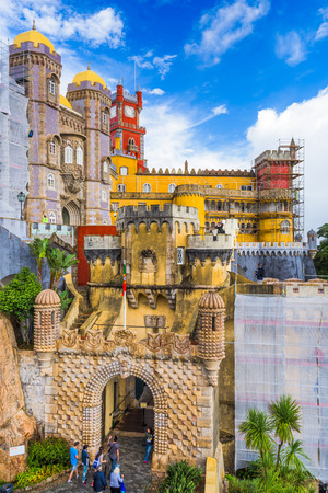 the pena national palace: SINTRA, PORTUGAL - OCTOBER 18, 2014: Tourists walk under scaffolded structures at Pena National Palace.