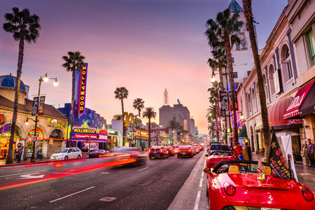 LOS ANGELES, CALIFORNIA - MARCH 1, 2016: Traffic on Hollywood Boulevard at dusk. The theater district is famous tourist attraction. Редакционное