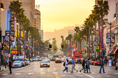 fame: LOS ANGELES, CALIFORNIA - MARCH 1, 2016: Traffic and pedestrians on Hollywood Boulevard at dusk. The theater district is famous tourist attraction.