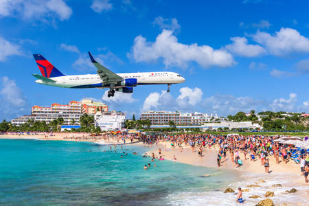 PHILIPSBURG, SINT MAARTEN - DECEMBER 28, 2016: A commercial jet approaches Princess Juliana airport above onlooking spectators. The short runway gives beach goers close proximity views of the planes.
