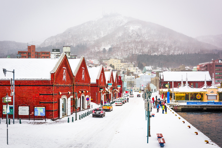 HAKODATE, JAPAN - FEBRUARY 2, 2017: Tourists enjoy a snowy day at historic Kanemori warehouse district. Hakodate Port was among the first Japanese ports to be opened to international trade.