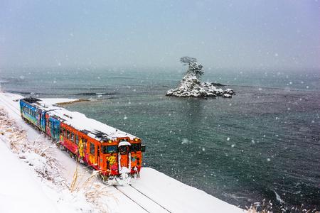 quasi: Amaharashi Coast Quasi-national Park, Japan - JANUARY 23, 2017: A Himi Line Train passes the Amaharashi Coast during winter.