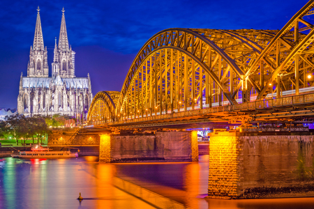 st german: Cologne, Germany old town skyline at Cologne Cathedral and Hohenzollern Bridge.