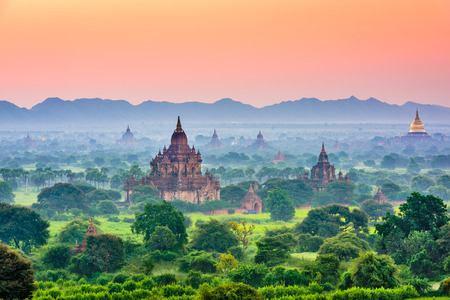 Bagan, Myanmar ancient temple ruins landscape in the archaeological zone at dusk.