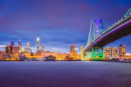 Philadelphia, Pennsylvania, USA skyline on the Delaware river with Ben Franklin Bridge at night.