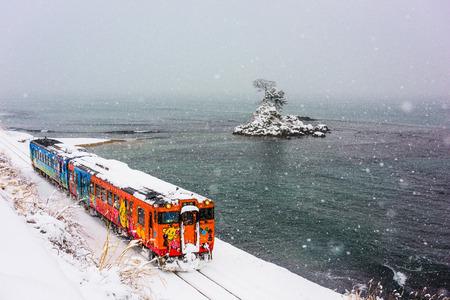 Amaharashi Coast Quasi-national Park, Japan - JANUARY 23, 2017: A Himi Line Train passes the Amaharashi Coast during winter.