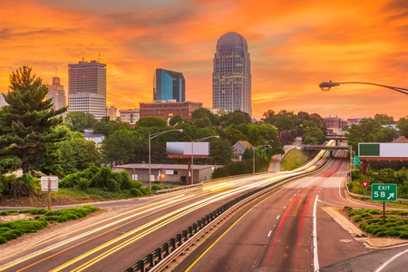 Winston-Salem, North Carolina, USA skyline and highways at dusk.