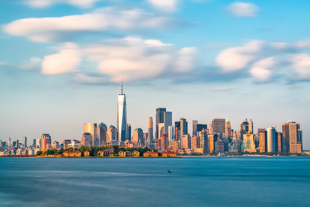 New York, New York, USA skyline from the harbor with Ellis Island. Imagens