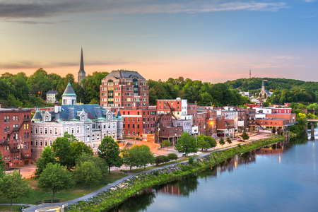 Augusta, Maine, USA town skyline on the Kennebec River at dusk.