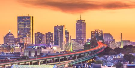 Boston, Massachusetts, USA skyline with bridges and highways at dusk.