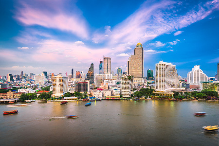 Bangkok, Thailand cityscape on the river at dusk.