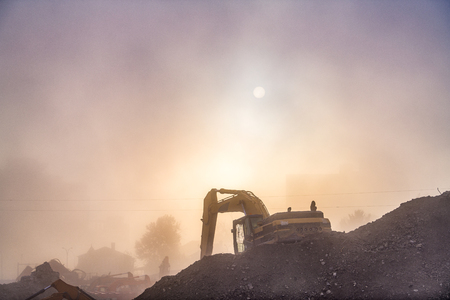 A construction vehicle works in the dusk and haze. 版權商用圖片