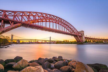 New York, New York, USA à Hell Gate Bridge au coucher du soleil sur l'East River. Banque d'images