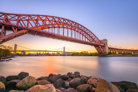 New York, New York, USA at Hell Gate Bridge at sunset over the East River. Imagens
