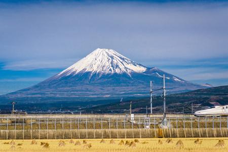 Mt. Fuji in Japan mit Ackerland und vorbeifahrendem Zug. Editorial