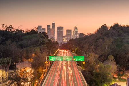 Los Angeles, California, USA skyline and highway at dusk. Редакционное