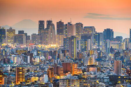 Tokyo, Japan cityscape with Shinjuku Ward and Mt. Fuji in the distance at dusk.