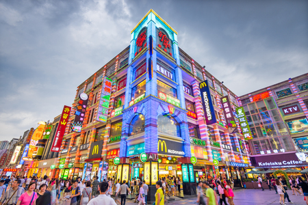 GUANGZHOU, CHINE - 25 MAI 2014 : les piétons traversent la rue piétonne Shangxiajiu. La rue est le principal quartier commerçant de la ville et une attraction touristique majeure.