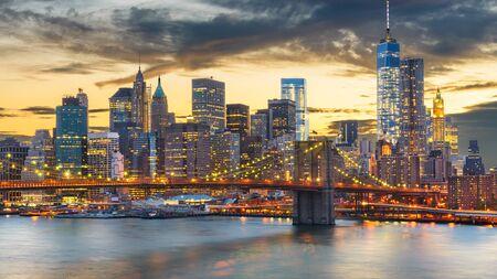 New York, New York, USA Skyline der Innenstadt von Manhattan über den East River mit der Brooklyn Bridge in der Abenddämmerung.