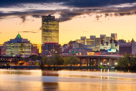 Albany, New York, USA skyline on the Hudson River at sunset.