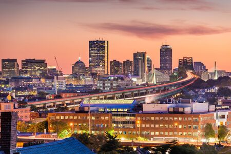 Boston, Massachusetts, USA skyline with bridges and highways at dusk.