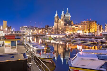 Amsterdam, Netherlands city center view with riverboats and the  Basilica of Saint Nicholas at night. 免版税图像