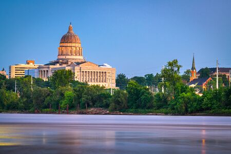 Jefferson City, Missouri, USA downtown view on the Missouri River with the State Capitol at dusk.