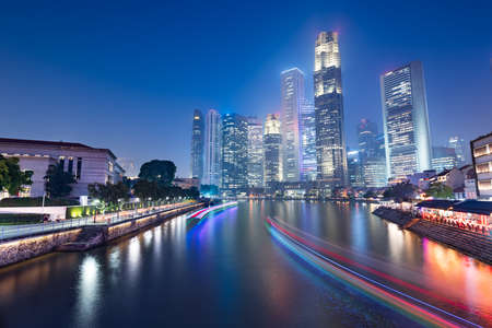 Singapore skyline and canal at night.